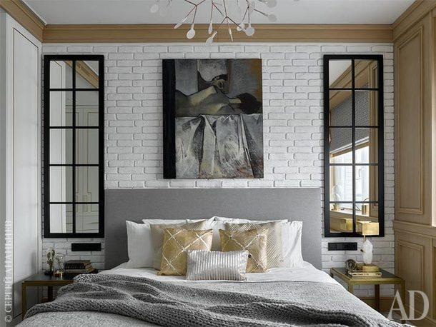 Спальня. Текстиль на кровати поддерживает игру с фактурами: плед крупной вязки и шелковые подушки эффектно смотрятся на фоне кирпичной стены.