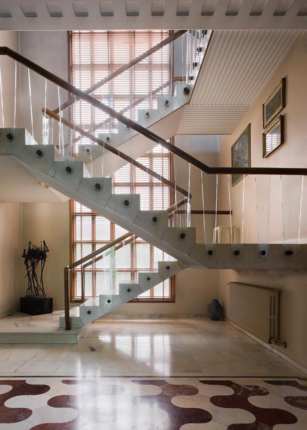 Гостиная наполнена множеством деталей. Пол из резного мрамора. Лестница, которая выглядит весьма современно, выполнена из мрамора, стекла имассива ореха (из него изготовлены перила).