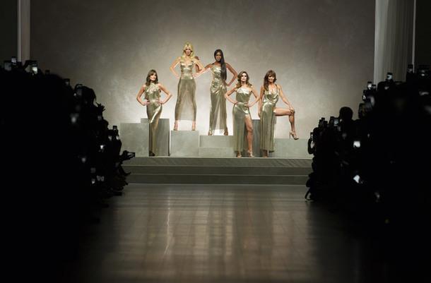 Карла Бруни, Клаудия Шиффер, Наоми Кэмпбелл, Синди Кроуфорд и Хелена Кристенсен на шоу Versace весна–лето 2018. В память обрате Донателла повторила знаменитый снимок, сделанный в 1990-х, с супермоделями в золотых платьях.