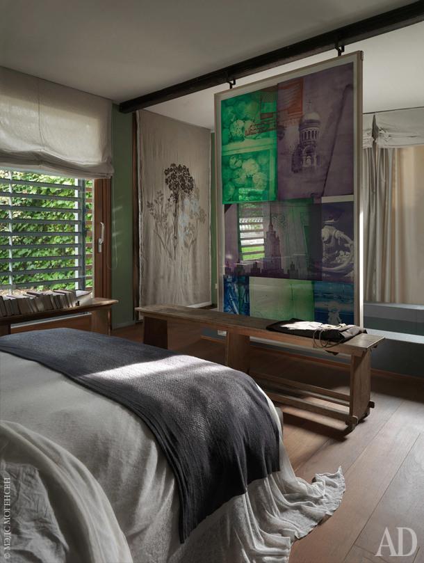 Спальня. За скамьей визножье кровати находится небольшой бассейн в окружении предметов искусства. На стене слева — панно 1867 года, а на переднем плане подвешенный на металлических направляющих принт Роберта Раушенберга.