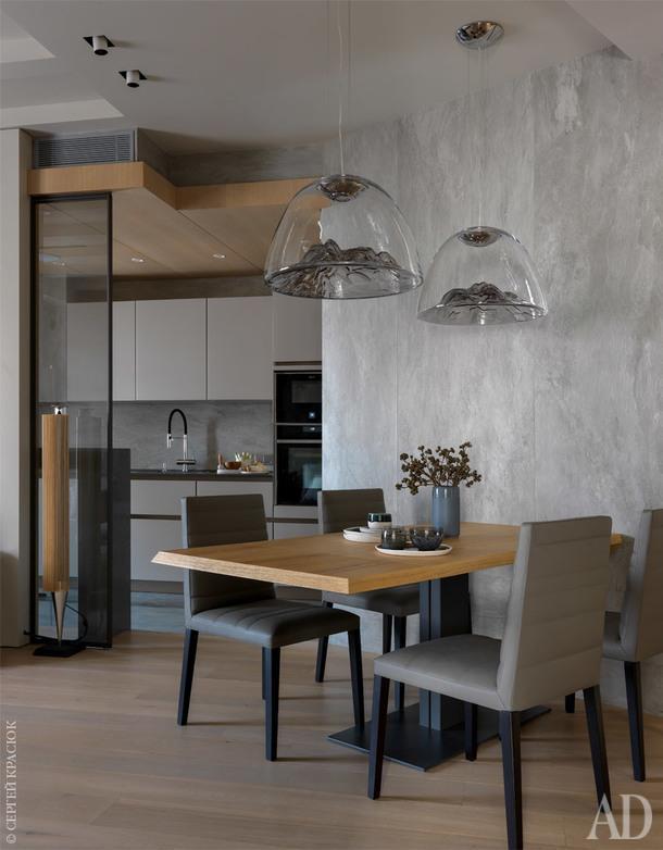 Вид из гостиной-столовой на кухню. Заказчики просили сделать два входа на кухню, в связи с этим в общем пространстве появилась перегородка со стеклянной вставкой.