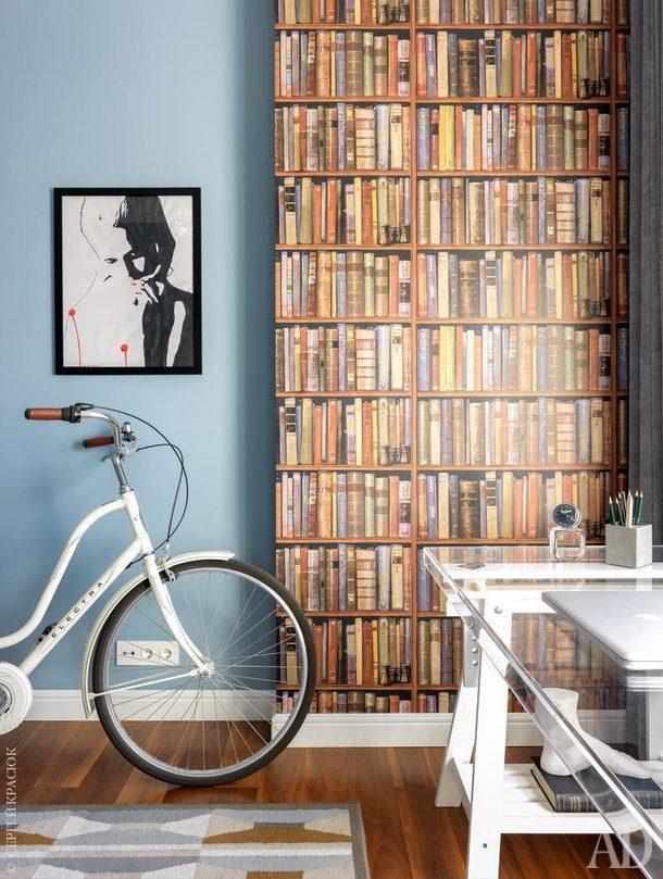 Фрагмент кабинета. Обои с изображением книг, Andrew Martin. Велосипед, который хранится здесь зимой, выглядит как арт-объект; рабочий стол у окна сделан из листа плексигласа, положенного на опоры из ИКЕA.