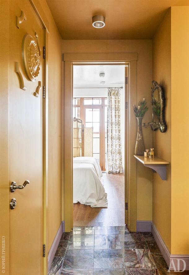 Прихожая. Полвыложен натуральным камнем. Дверь украшена гипсовой лепниной. Краска здесь и в других комнатах, Farrow &Ball. Надальнем плане спальня. Присоединить к ней балкон было невозможно, нодизайнеры заменили балконную дверь, чтобы впустить вкомнату побольше света.