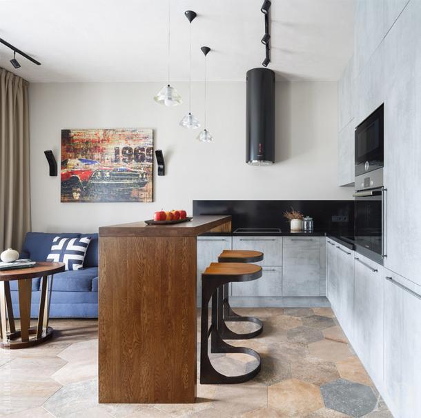 Кухня выполнена на заказ по эскизам авторов проекта, отделка под бетон, столешница — искусственный камень, барная стойка — массив дерева. Диван, барные стулья, столик, постер на стене, My America; подвесные светильники и бра на стене, Cosmorelax; керамогранит на полу, Ascot Ceramiche; декор, Crate&Barrel.