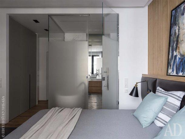 Ванную и спальню разделяет стеклянная перегородка. Слева виден встроенный шкаф, его сделали на заказ.