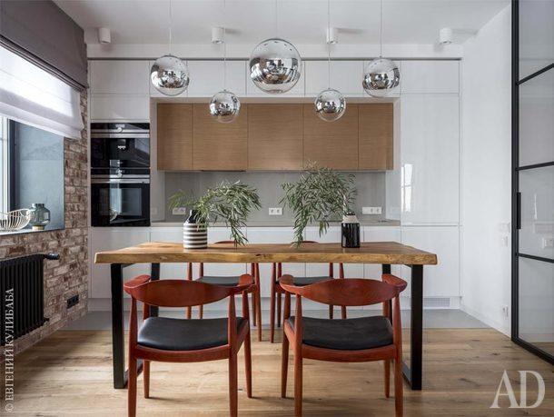 В столовой обеденный стол из деревасуар, сделанный на заказ, стулья по дизайну ХансаВагнера и светильники Tom Dixon.