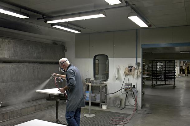 Лакокрасочный цех. Во влажной камере мастер распыляет краску вручную на несерийные элементы.