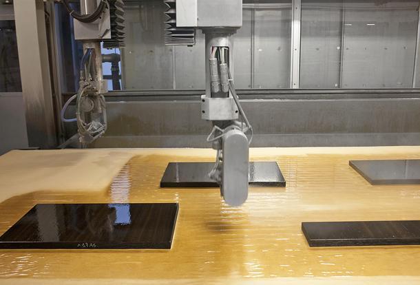 Крупный план станка для лакировки. Компьютер определяет положение и размер деталей, наносит лак иотправляет насушку в печь.