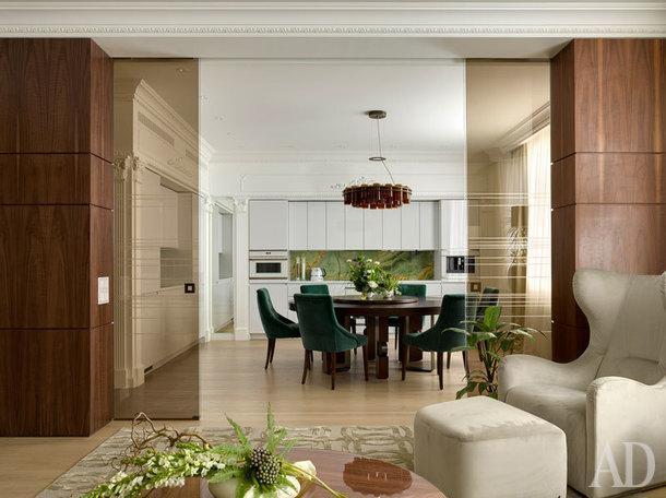 Вид из гостиной на кухню. Обеденный стол, люстра, кресло и пуф Smania, стулья Porada, кухня Hacker, раздвижные стеклянные двери и стеновые панели изготовлены на заказ.