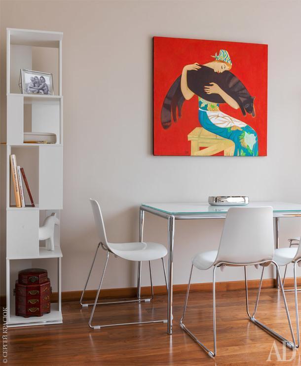 Интерьер квартиры построен на контрасте светлых монохромных поверхностей стен и мебели с насыщенным орехом пола и дверей. Яркая и масштабная живопись нарушает меланхоличное спокойствие сдержанной цветовой гаммы кухни-столовой.