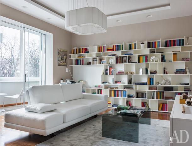 Гостиная-кабинет — центр всего дома, а центр гостиной — небольшой, но эффектный диван Rolf Benz. Яркие корешки книг в сочетании с хаотичным по внутренней архитектуре стеллажом Cattelan превращают стену в бодрую графическую композицию.