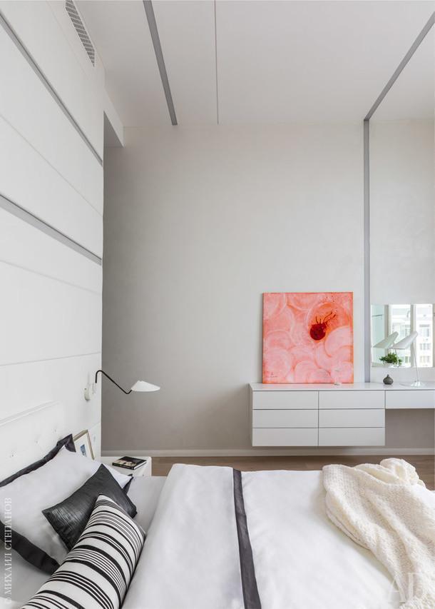 Спальня. Стена за изголовьем кровати от пола до потолка оформлена панелями, обитыми белой кожей. Прямо в них интегрировано линейное освещение: светильники, Panzeri. Настольный светильник, Vibia.
