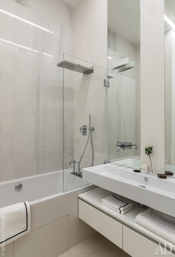 Высота потолков в ванной комнате подчеркивается с помощью зеркал и линейных светильников. Сантехника, Villeroy & Boch, Cerasa; смесители, Antonio Lupi. На стенах в ванной использована крупноформатная плитка от Archskin.