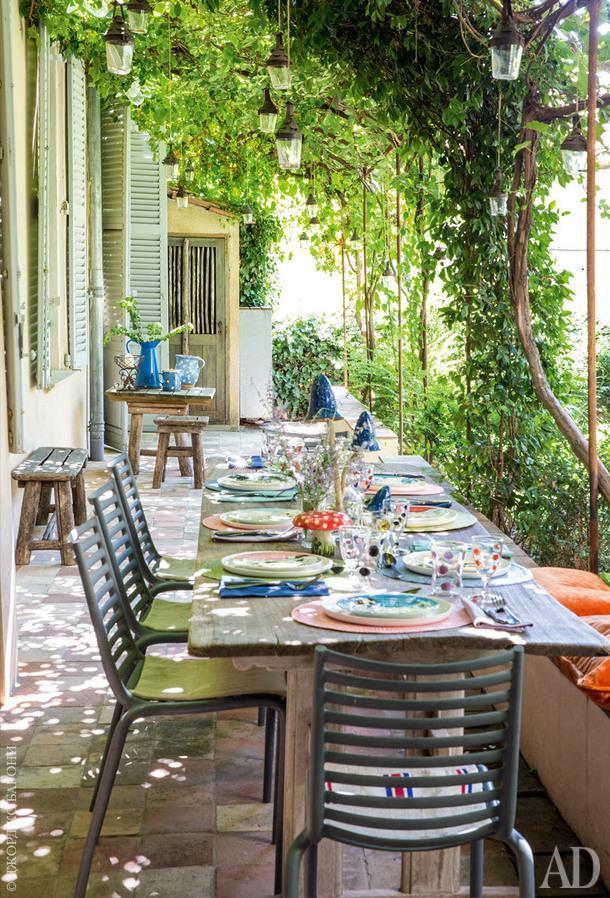 Внутренний дворик. Стол подизайну студии ALM; пластиковые стулья подизайну Филиппа Старка; стаканы настоле, Vetrofuso; остальная посуда винтажная.