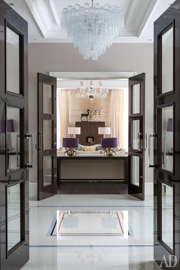 Вид из столовой на гостиную. Все помещения имеют одну общую ось, которую архитекторы подчеркнули одинаково оформленными проемами и люстрами. Люстра в Холле Bella Figura.