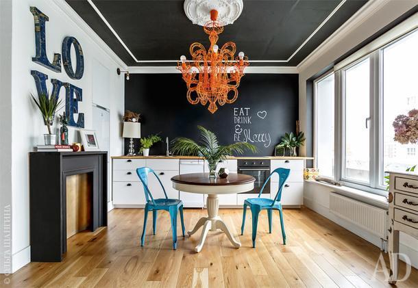 Кухня-столовая. Кухонный гарнитур купили в IKEA. Стена за ним покрыта краской для грифельных досок— этолюбимый прием авторов проекта, которые используют эту поверхность для составления всевозможных списков. Люстру купили на Бали, но включают ее редко, предпочитая боковой инижний свет.