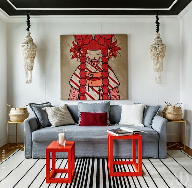 В гостиной — картина неизвестного художника исветильники из ракушек сБали. Диван иковер изIKEA. Черный потолок, как объясняют хозяева, придает комнате интимность.