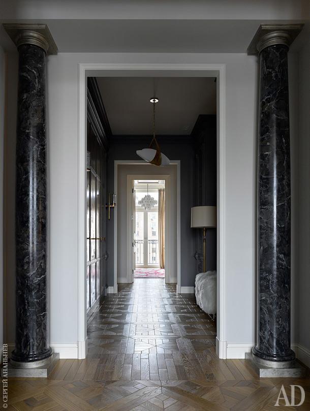 Проходной коридор, соединяющий общественную зону с приватной (слева разместилась большая гардеробная, справа — библиотечные шкафы с зеркалом в пол). Колонны — гипс, Мастерская
