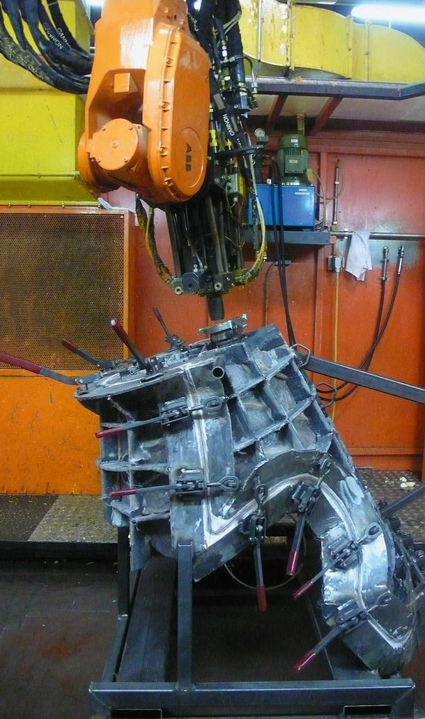 Робот вливает жидкий пенополиуретан в форму.