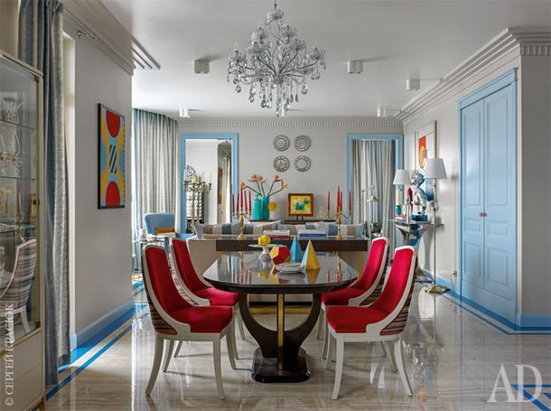 Обеденный стол освещает люстра из голубоватого чешского стекла. На полу керамогранит под оникс, Atlas Concorde. Стулья заказаны в Испании, но перетянуты кораллово-красной тканью, а их каркас покрашен в светло-серый цвет, в тон стенам.