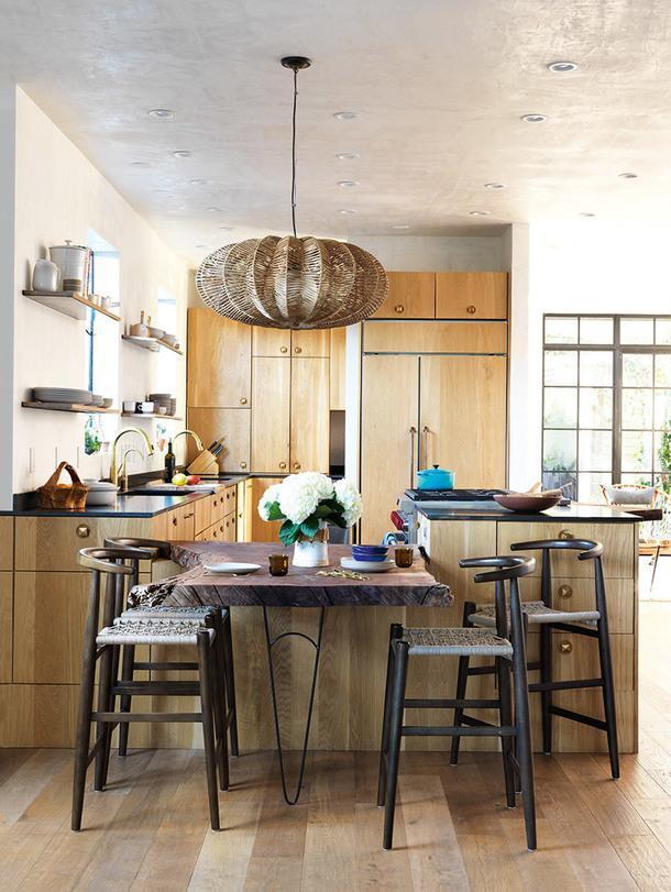Кухонная мебель сделана измассива французского дуба, а рабочие поверхности — из черного гранита. Смесители, Dornbracht. Барные стулья, west elm.
