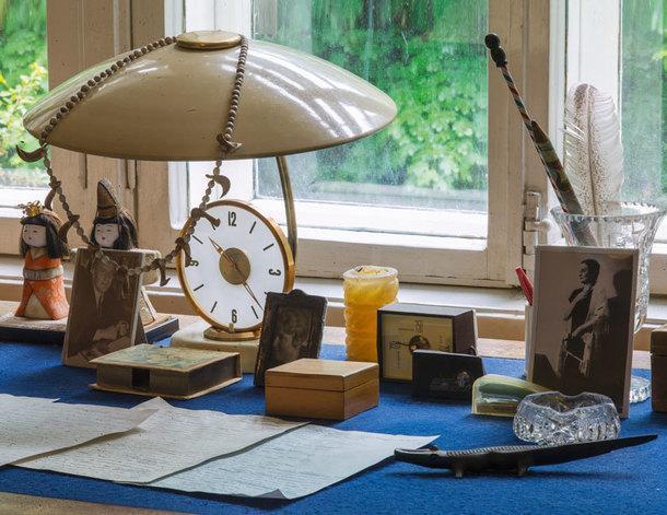 На письменном столе писателя — портрет Анны Ахматовой, два крокодила— один мраморный, другой из черного дерева, камень, который привез из Новой Зеландии исследователь Африки Андрей Капица, и еще ворох памятных мелочей.