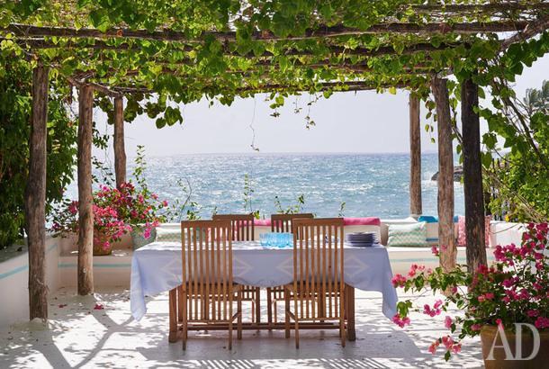 На этой тенистой террасе часто накрывают стол для ланча. Отсюда видно море и частный пляж, который находится внизу. Текстиль, Quadrille.