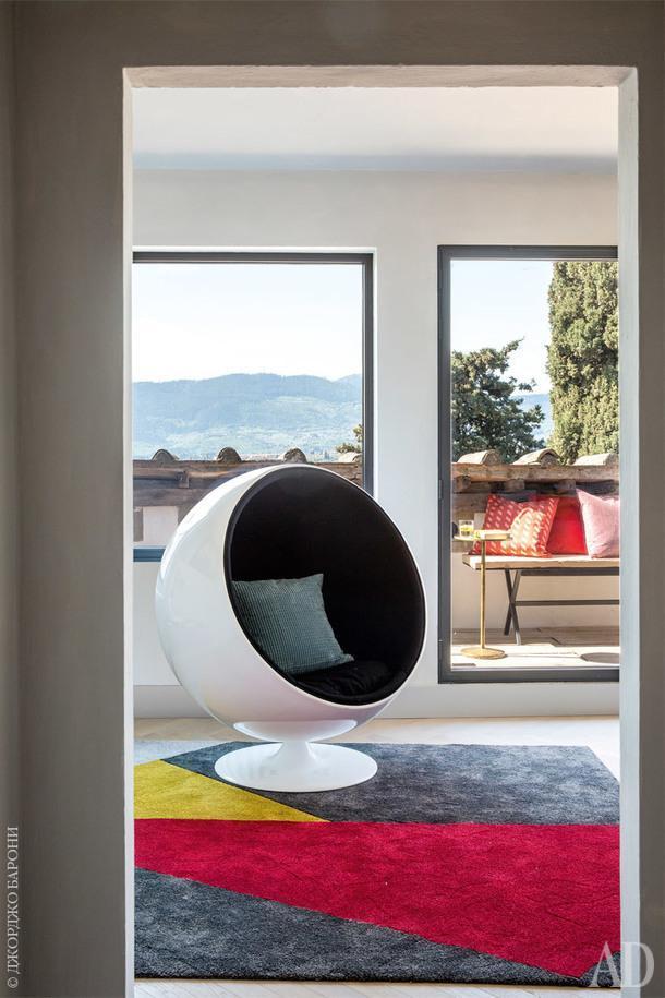 Небольшая зона отдыха, смежная сгостиной. Увинтажного кресла Ball 1963года по дизайну Эро Аарнио сохранилась родная обивка. Рамы панорамных окон сделаны изметалла.