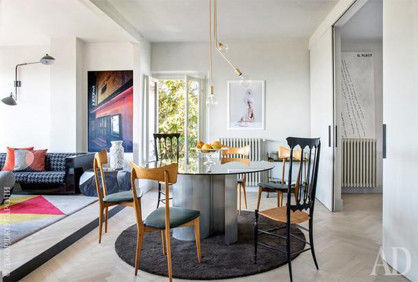 Зона столовой. Обеденный стол 1970-хгодов; стулья по дизайну Ико Паризи 1960-х годов; между ними два стула Chiavari начала XXвека; ковер подизайну ABarchitects; автор фотографии на стене— ВирджинияПаники. Справа находится кухня, которая отделяется раздвижнымидверями.