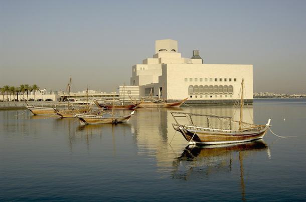 Старые лодки ловцов жемчуга на фоне Музея исламского искусства в Дохе.