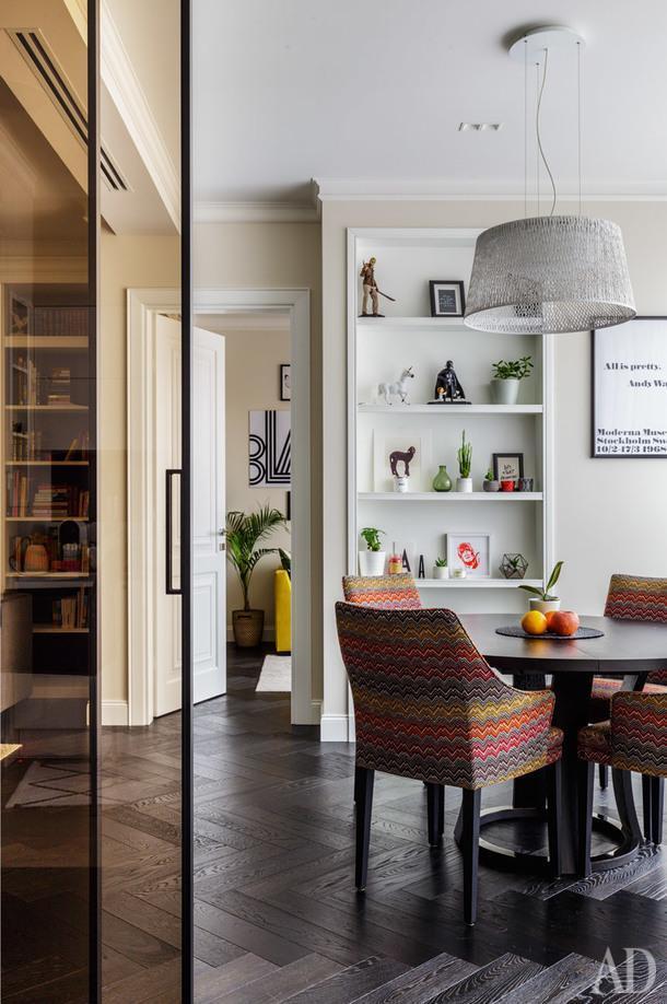 """Вид из кухни на столовую зону. Стол, Potocco; стулья Jab Furniture; светильник, Vibia; стеклянная перегородка, Rimadesio; белая дверь, Garofoli; стеллажи сделаны по эскизу дизайнера компанией """"Ольха Декор""""; паркет, Solid Floor."""