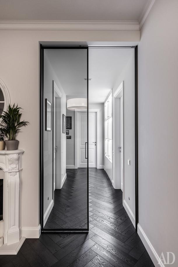Вид из гостиной на коридор. Раздвижная перегородка, Rimadesio; межкомнатные двери, Garofoli; паркет, SolidFloor. По правой стене— встроенные витрины, где расположилась часть коллекции фигурок супергероев.