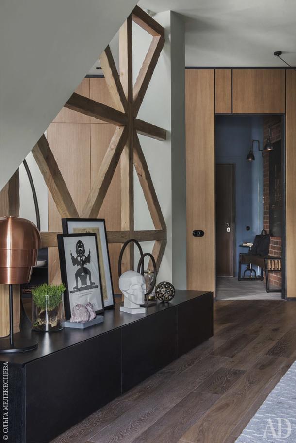 Вид из гостиной на прихожую. Модуль под ТВ и стеновые деревянные панели с металлическими вставками изготовлены на заказ по эскизам дизайнера. Светильник, BoConcept.