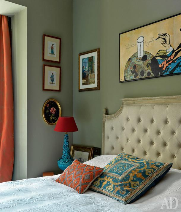 Фрагмент спальни. Сбоку от кровати гравюры скостюмами жителей Калуги. Подушка расшита тарусским крестом.