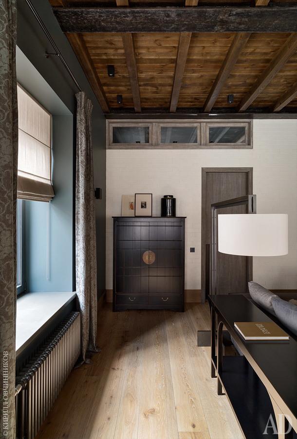 Фрагмент гостиной. Окна под потолком впускают свет в прихожую. Шкаф иконсольный столик за диваном,Luciano Zonta. Шторы, deLeCuona. Торшер,Liaigre.