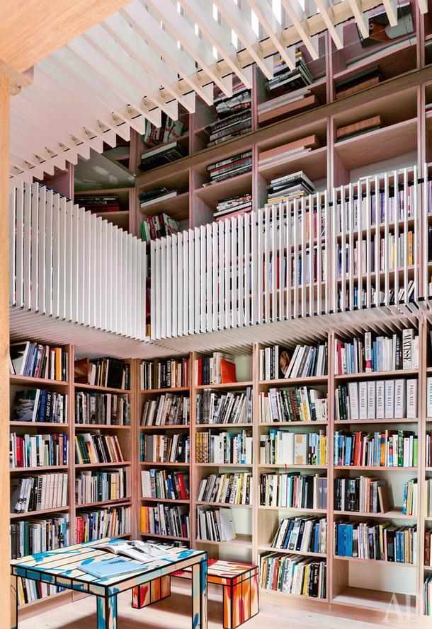 Библиотека. Стеллажи занимают весь периметр комнаты. Зеркало на потолке создает иллюзию двухуровневого пространства. Стол и скамья по дизайну Ричарда Вудса.