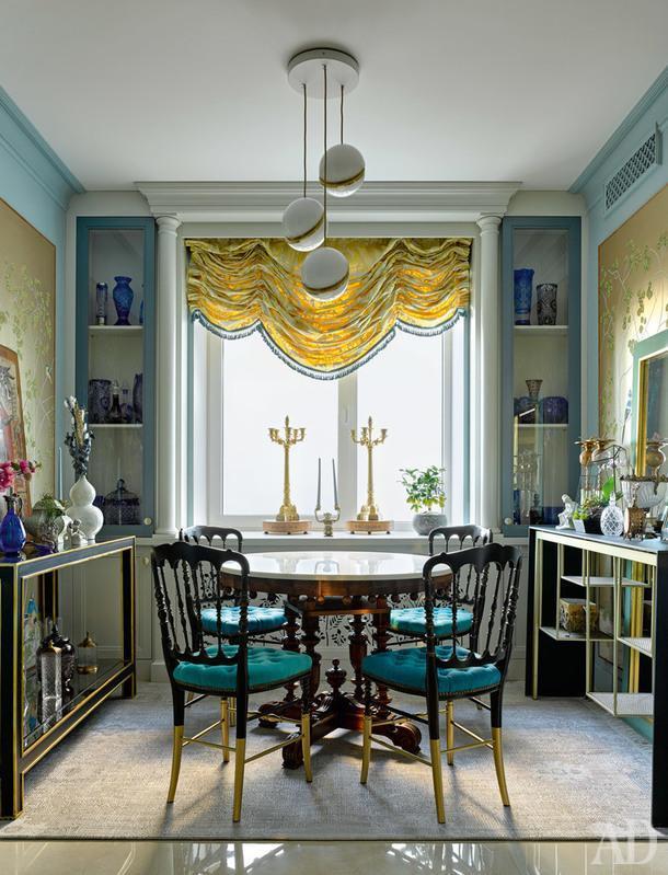 """Похожую на пенал кухню разбили на две части: зона готовки расположена ближе ко входу, а у окна— стол для завтраков. Он имеет антикварное основание иновую столешницу. Стулья остались от прежнего интерьера, но были перекрашены. Справа консоль, MOGG; позолоченные антикварные подсвечники, """"Русская усадьба""""; синее стекло изколлекции хозяйки."""