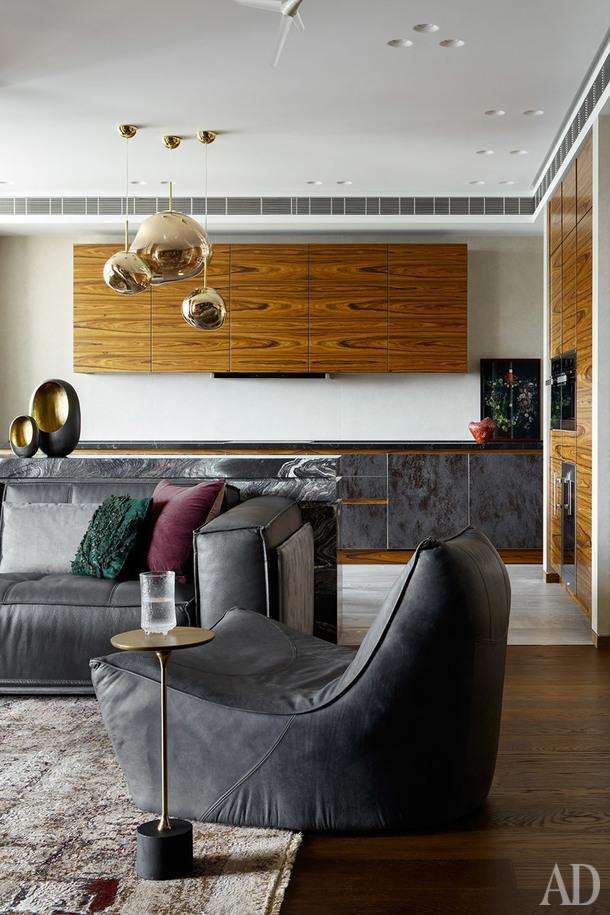 Гостиная и кухня. Кухня, Giulia Novars; стойка из мрамора, Chipollo.На стенах крупноформатный керамогранит от Archskin. Диван