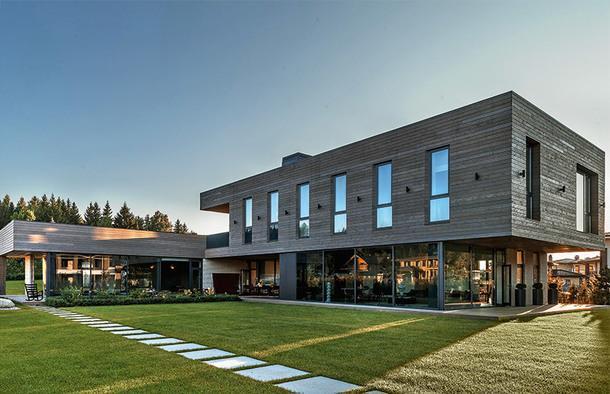 Фасад дома. Остекление сделали на фабрике, Aluma; пол и фасад обшиты лиственницей.